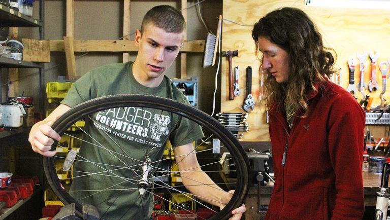 Badger Volunteer repairs bike