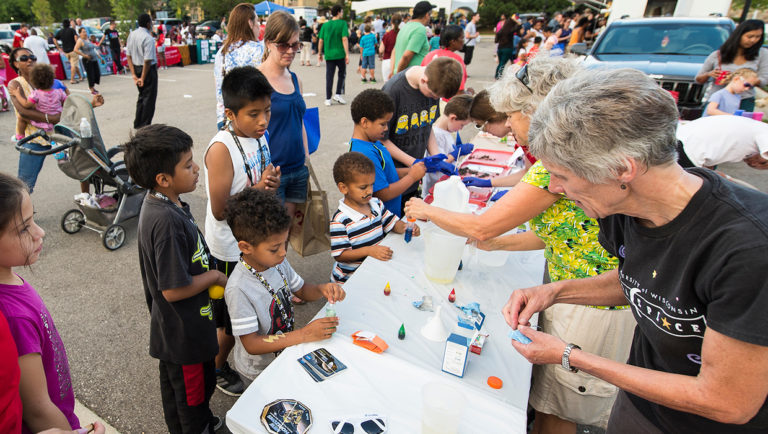 Children learn to make tubes of liquid lava at a UW Space Place-sponsored table
