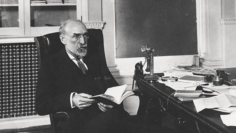 Charles Van Hise reading at his desk