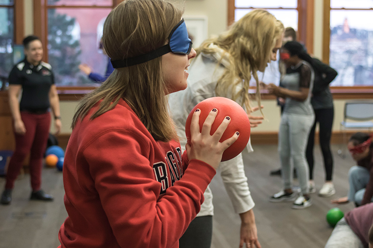 Students are blindfolded and are commanded by their partner to grab a nearby ball to throw at other blindfolded students.