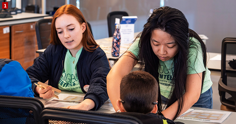 Badger Volunteer Lizzie Peterson (left) and Vera Wei (right) help facilitate science activities for elementary and middle school students at the Discovery Building.