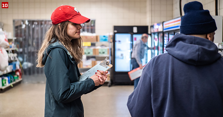 Badger Volunteer Katelyn Condon assists a customer as they shop through St. Vincent De Paul, a food pantry that allows customers to shop for about five days' worth of groceries.