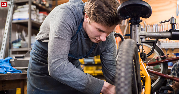 Badger Volunteer James Curliss repairs a bike tire at Wheels for Winners, a nonprofit organization that provides bicycles to youth who are positive influences in their communities.