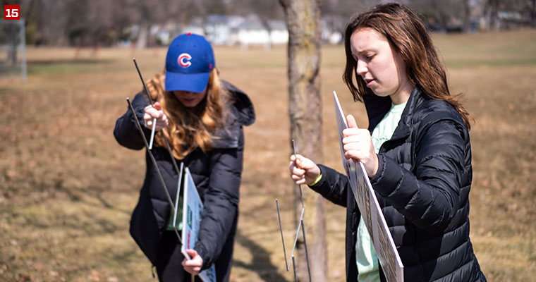 Badger Volunteer Ellie Stark (left) and Morgan Kamholz (right) putting together sustainability signs at Wingra Park.