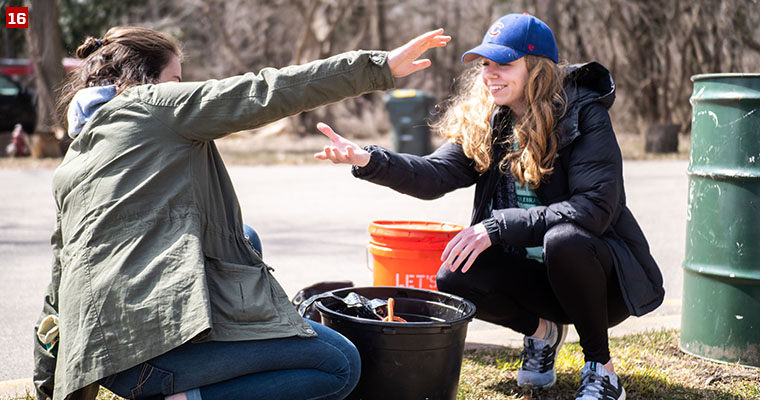 Badger Volunteer Taylor Madl (left) and Ellie Stark (right) giving each other a helping hand at Wingra Park.
