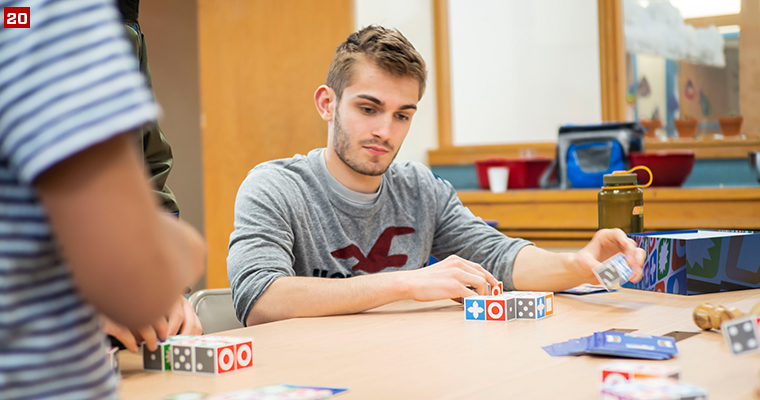 Badger Volunteer Brett Danen plays a puzzle game with students at the Bayview Foundation, a nonprofit organization that provides affordable housing and supportive services to approximately 300 low-income residents, primarily immigrants and refugees.