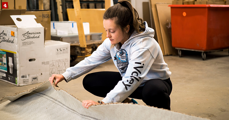 Badger Volunteer Kelsey Hickok helps roll up a rug at Habitat ReStore, a nonprofit that aims to build homes, communities and hope, locally and around the world.