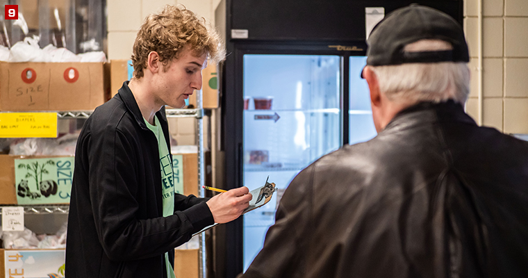 Badger Volunteer Ben Koziol assists a customer as they shop through St. Vincent De Paul, a food pantry that allows customers to shop for about five days' worth of groceries.