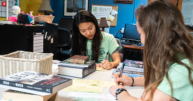 Badger Volunteers Shuka Konishi (left) and Mikayla Sandin (right) responding to a letter from an incarcerated LGBTQ+ people at LGBT Books to Prisoners, a trans-affirming, racial justice-focused, prison abolitionist project that sends books to incarcerated LGBTQ-identified people across the United States.