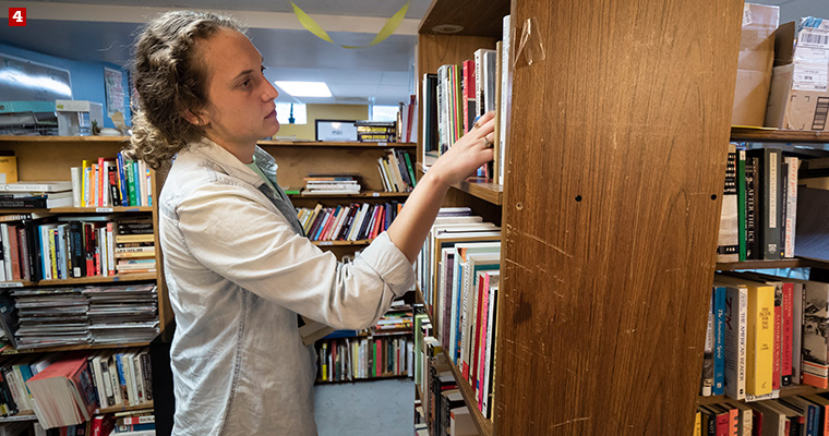 Badger Volunteer Leah Piehl searches for a book requested by incarcerated LGBTQ+ people at LGBT Books to Prisoners, a trans-affirming, racial justice-focused, prison abolitionist project that sends books to incarcerated LGBTQ-identified people across the United States.