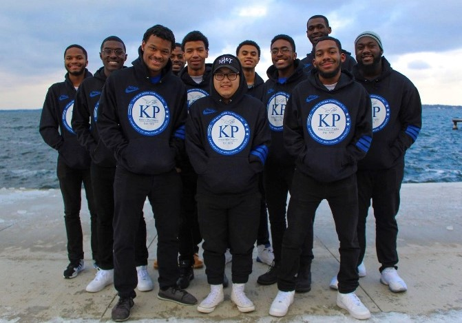 Smiling fraternity brothers in front of lake wearing Kappa Rho sweatshirts